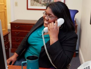 Image of a fat woman talking on the phone in an office setting.